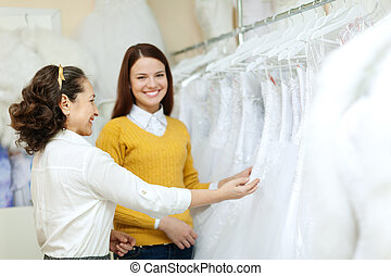 Two women chooses bridal gown at shop of wedding fashion