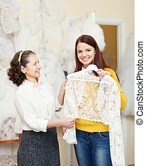 bridesmaid with bride chooses bridal clothes at shop of...