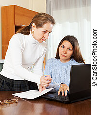 mature woman and yong daughter with notebook