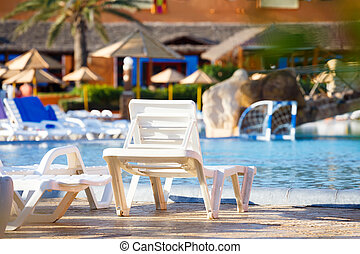 sunloungers on swimming pool