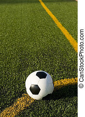 Soccer ball and football on a field - A soccer ball or...
