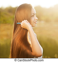 beautiful girl combs her hair Asian appearance