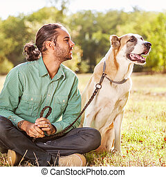 Man and central Asian shepherd walk in the park. He keeps the do