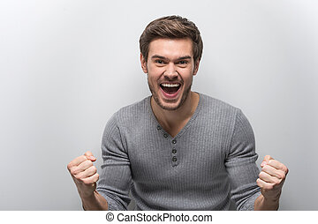 Portrait Of Smiling Man With Fists Up. happy guy standing...