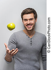 Portrait of handsome unshaven man smiling guy throwing apple...