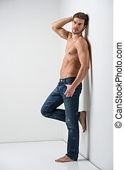 Healthy muscular young man in jeans. Isolated on white background guy leaning on wall