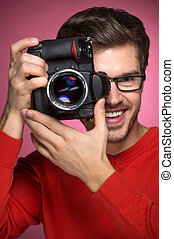 Portrait of young male with professional digital camera. man in glasses standing over red background and making shots