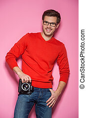 Portrait of young male with professional digital camera. man in glasses and jeans standing over pink background.