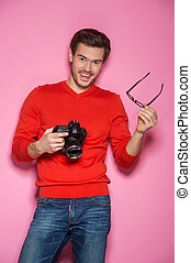 Portrait of young male with professional digital camera. man removed glasses standing over pink background.