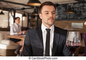 Stylish young man sitting in bar. Handsome man drinking...