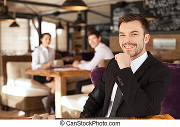 Stylish young man sitting in restaurant. closeup of handsome...