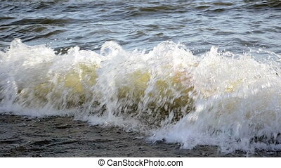 Waves splash on pebble sea shore