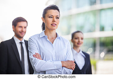 Three smiling business people standing outside waist up of...