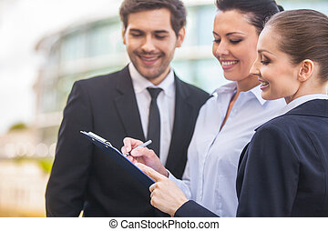 Young smiling business women and business man three people...