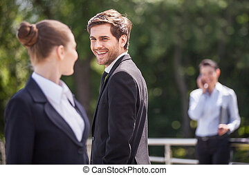 Three happy business partner people talking outside brunette...