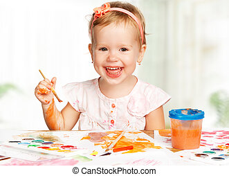 happy child girl draws paints - happy baby child girl draws...