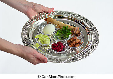 Passover Seder Plate - Jewish woman hands carry Passover...