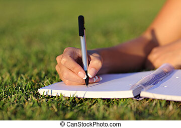 Close up of a woman hand writing on a notebook outdoor lying...