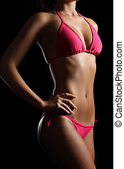 Perfect fitness body wearing a pink bikini on black -...