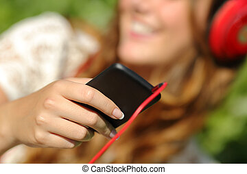 Woman hand using a smart phone to listen to the music with...