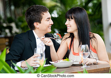 Couple Eating Outdoors - An attractive young couple shares a...