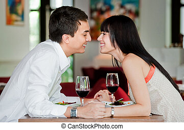 Couple Kiss Over Meal - A young and attractive couple...