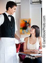 Waiter Serving Coffee - A young and attractive waiter...