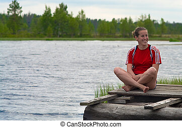 Resting near the water - Young woman seats on the edge of...