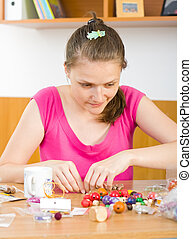 Art and hobby - A young woman working with her beads ,...