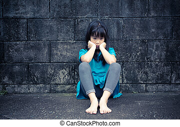 portrait of a sad Asian girl against grunge wall background