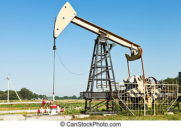 pumpjack pumps oil in Kuban region, Russia in summer day