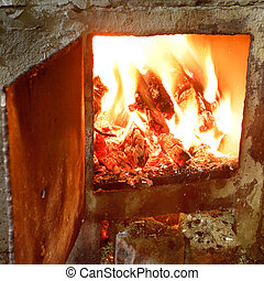 burning wood in furnace with open door close up