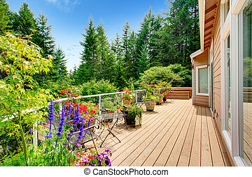 Wooden walkout deck with vibrant color flowers - Walkout...