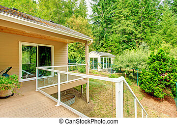 Wooden walkout deck with glass railing - Walkout deck with...