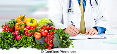 Nutritionist doctor man with vegetables working in the...