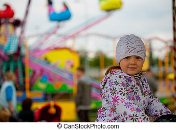 Little girl in amusement park - Cute little girl in...