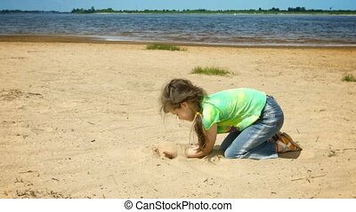 Little girl playing with sand on the shore of a large river