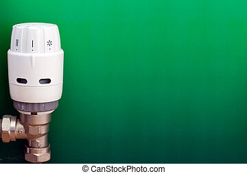 Green Energy - Radiator thermostat on a graduated green...