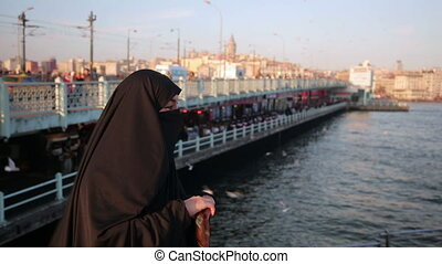 Woman dressed with black headscarf, chador eating, istanbul city