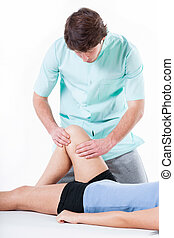 Physiotherapist diagnosing patient with painful knee