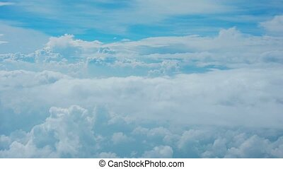 Clouds in the sky - view through glass of aircraft window