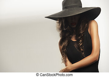 Beautiful young woman with red lips wearing summer black hat...
