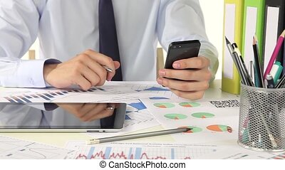 Businessman using a smartphone in the office - a young...
