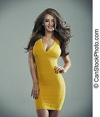 Happy blond woman in yellow dress in studio