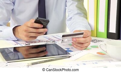Business man paying with credit card by smartphone -...