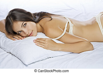 on pillow - Portrait of young beautiful woman on white sheet