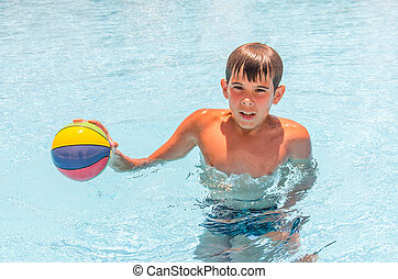 Boy with a ball in the pool