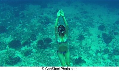 Girl pops up after a deep dive in the sea. Show that all is fine.