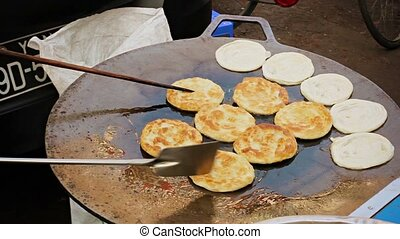 Cooking pancakes on the street for sale. Burma, Yangon -...