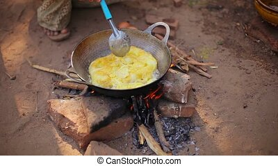 Local man prepares an omelet on a fire in the open air....
